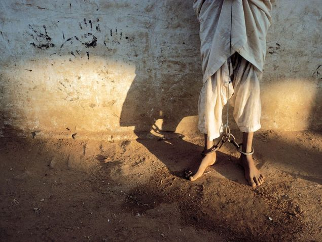 "Chained Feet, Sudan Photograph by Reza  This Month in Photo of the Day: Images From National Geographic Books  ""I saw his feet, scarred by chains that also bound his hands. His eyes were resigned, his violence contained.""—Reza   From the National Geographic book Reza War + Peace, 2009"