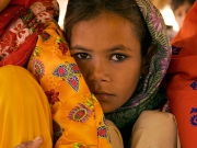 In this image, a Pakistani girl peers into the camera lens PHOTO by Annie Griffiths Belt