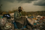 """Micah Albert, USA, Redux Images, 1st Prize Contemporary Issues Single. Taken on 03 April 2012 in Nairobi, Kenya. Pausing in the rain, a woman working as a trash picker at the 30-acre dump, which literally spills into households of one million people living in nearby slums, wishes she had more time to look at the books she comes across. She even likes the industrial parts catalogs. """"It gives me something else to do in the day besides picking [trash],"""" she said."""
