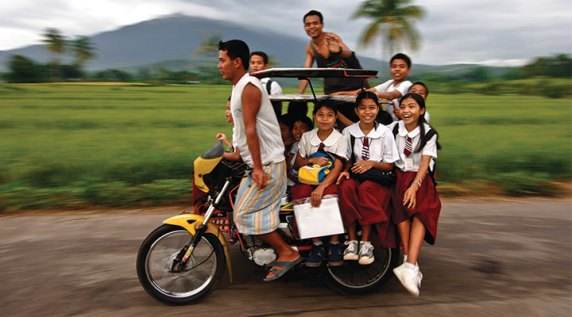 "Philippines: Children cram onto a small taxi called a ""tricycle"" for their ride to school. It costs them less than a dollar, but that's a lot for poor families to have to pay.(SOURCE: compassion.com)"