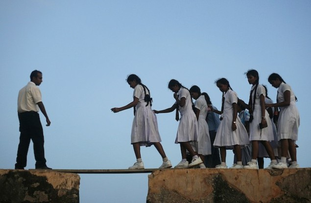 In Sri Lanka, a group of schoolgirls walk across a plank between the walls of the 16th-century Galle fort on July 8, 2009. (SOURCE: takepart.com)